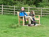 Grandad and Harvey sitting on Granny's bench - photo by Celia.  (Harvey's on the phone to his mum)