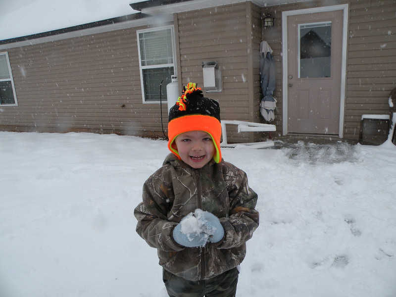 Michael gets ready to throw a snowball in their back yard.