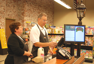 Owner Mike Schwartz and his wife, Rosanne, go over cashier procedures.
