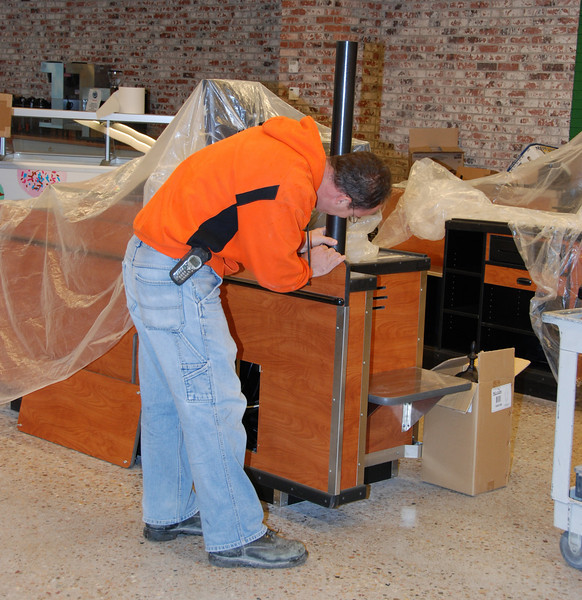 Matt from MCL Construction, site manager, puts finishing touches on the front registers.
