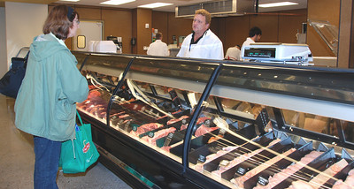 John assists a customer at the Wohlner's meat counter.