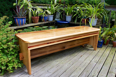 """My version of a """"Pontchartrain"""" bench. It is made of cypress with inlaid stripes of red cedar and some hidden struts of teak for added strength. I know I will have to refinish frequently, but I couldn't resist putting on the polyurethane."""