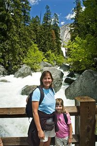 Steph and Sara standing on the bridge with Vernal Falls in the distance.  Our original intention was to just hike to this bridge, but we decided we'd continue on up and see how much closer we could get to Vernal Falls.  We could tell from hikers coming down that you would get very wet if you went all the way there.  Like all the other rivers, you can tell that this one is really full and foaming with major rapids.