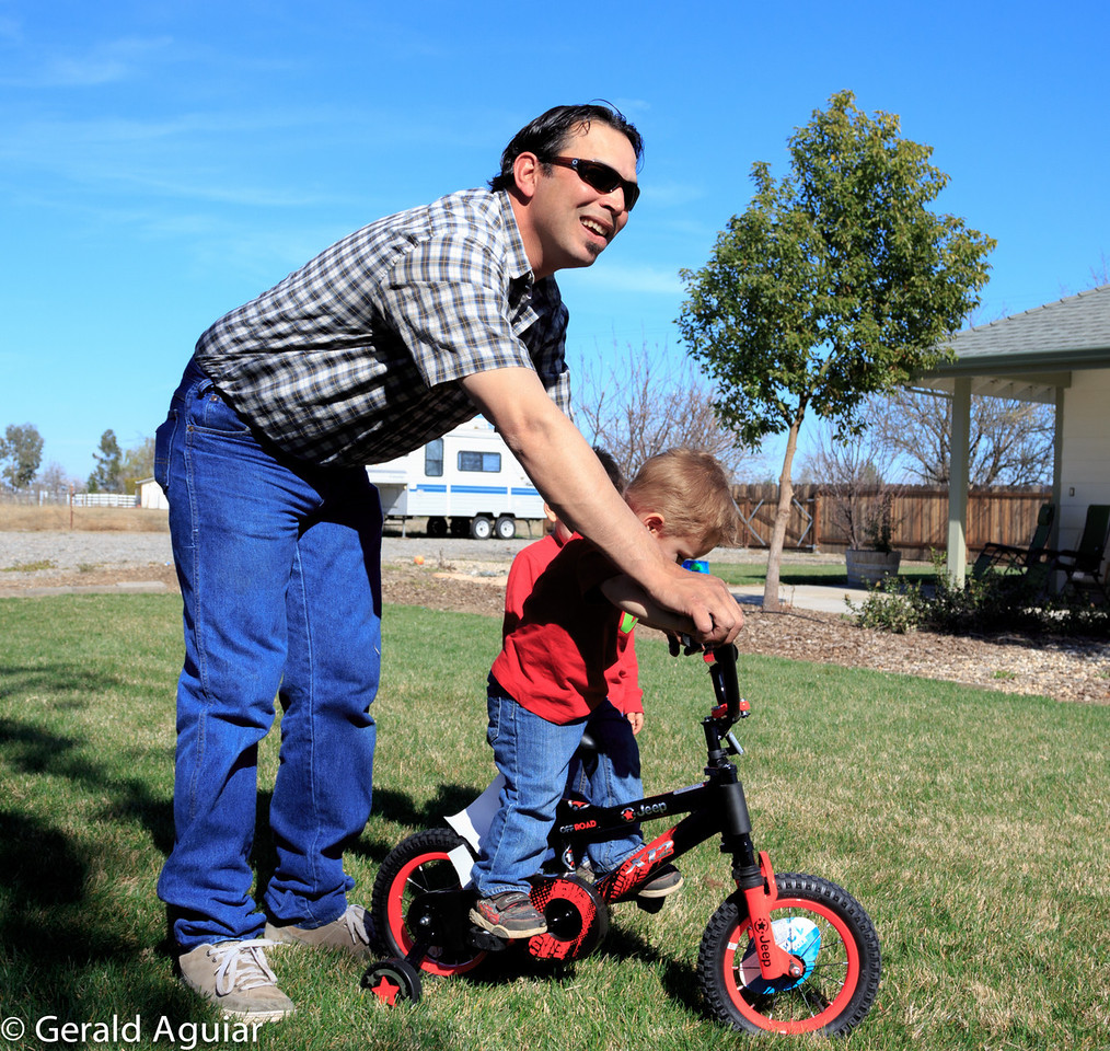 Mario helping Zane on his new bicycle.