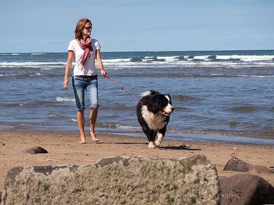 woman with dog on Robin Hoods Bay beach, Norh Yorkshire coas