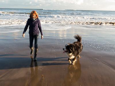 woman with dog on Robin Hoods Bay beach, Norh Yorkshire coas