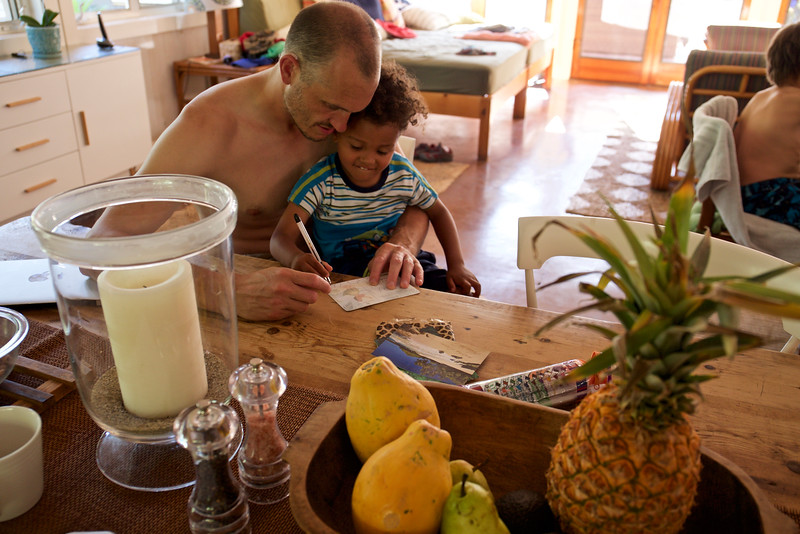 Jason helps Baye write his first postcard at the beach house.