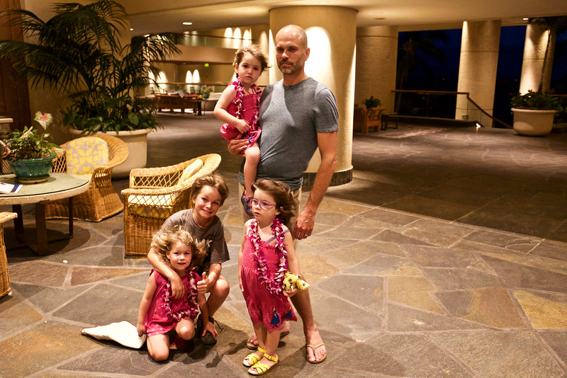 Justin with the triplets and nine-year-old Taio, waiting for their room keys, with the tradewinds of Kohala (Kamakani o Kohala) sweeping their hair.