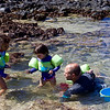 Baye and Clio admire the sea urchin; Justin holds Makeda and looks on.