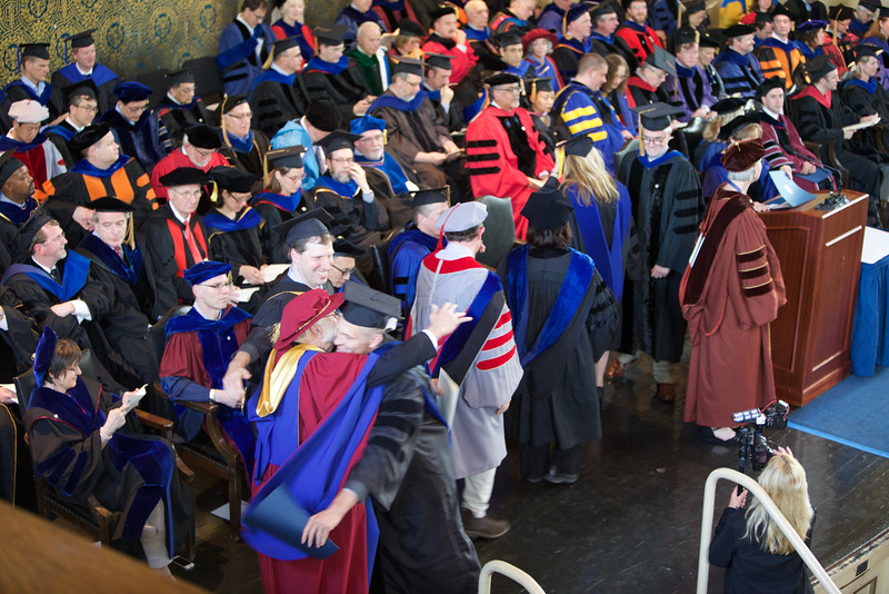 A hug from Dad!  <br /> Steve goes to greet Jason after he receives the diploma. Steve is dressed in his academic gowns from the University of British Columbia (1975).