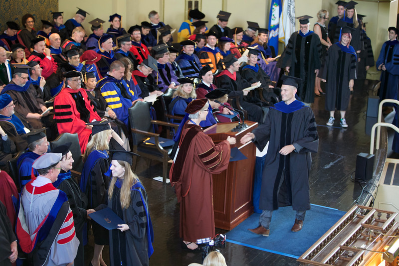 Jason receives his degree from Lynn Cooley, Dean of the Graduate School of Arts and Sciences.
