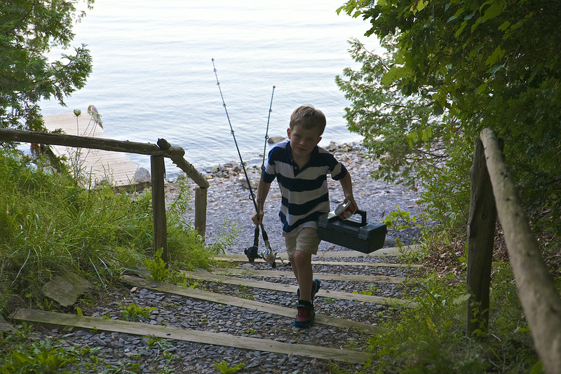 Taio proudly carries the fishing poles and tackle box up from the dock.