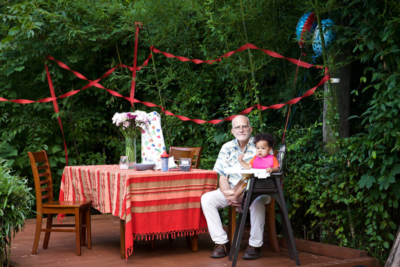 Grandpa sits with Masha  on the deck  in the garden. He brought two birthday balloons with him from Connecticut.