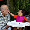 . . . Masha feeding Grandpa blueberries.