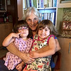Sarah hugging Anahita and Makeda in the kitchen at Puu Pueo<br /> (Note the photo of our last full family reunion in 1983.)