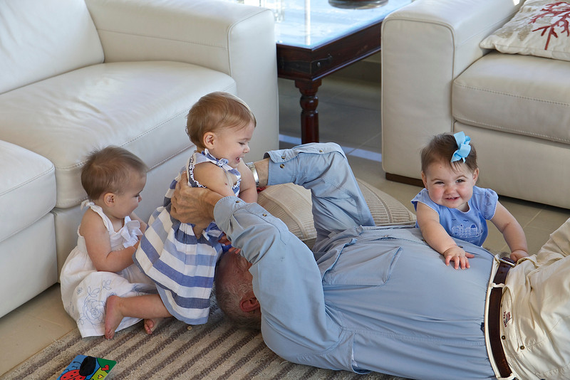 Steve being swarmed by grand-daughters Anahita, Clio and Makeda, almost one-year-old; Abu Dhabi.
