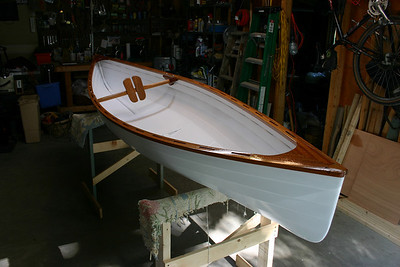"The finished canoe, with a small plywood ""seat"" and a back rest that rotates to fit each person. The canoe is paddled like a kayak, sitting on the bottom with a double bladed paddle. I use a small camping chair, which provides padding on the seat and back."