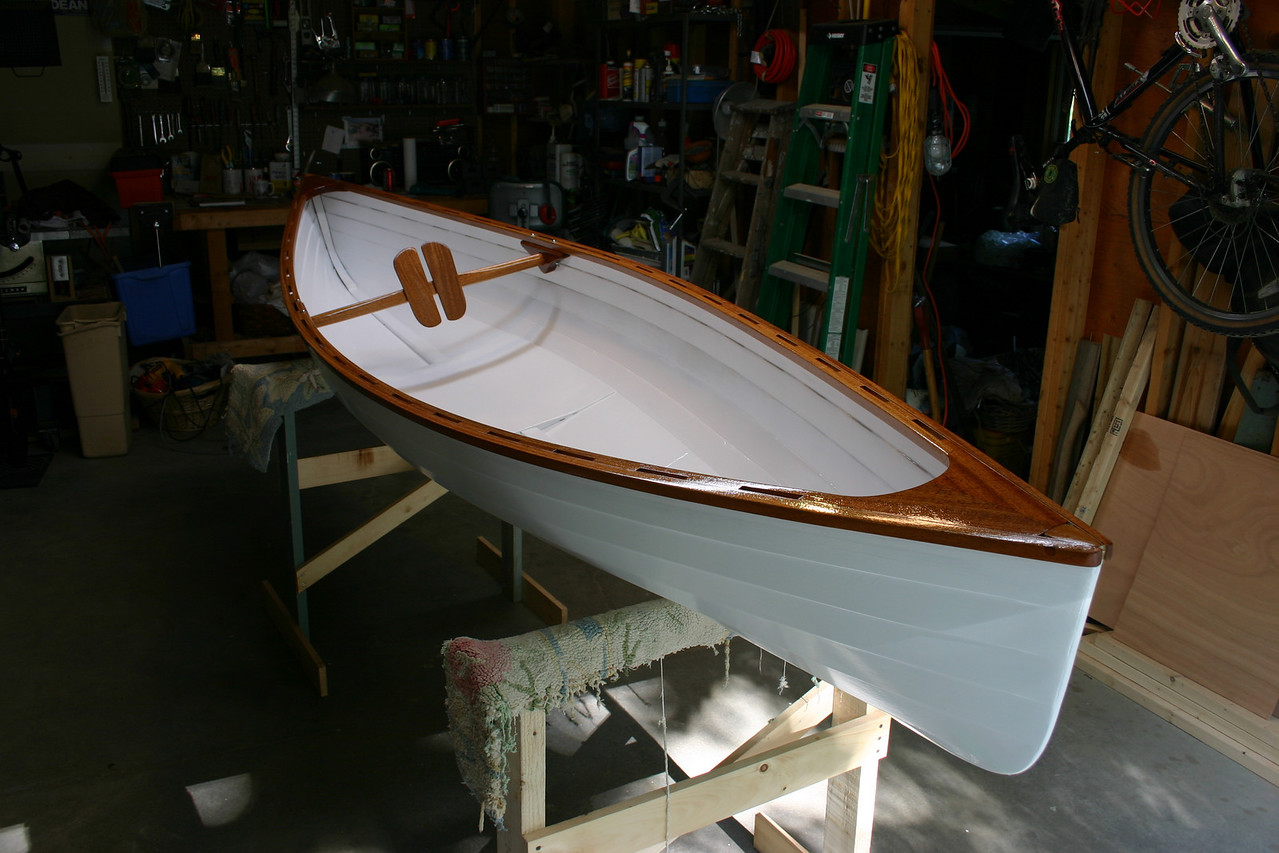"""The finished canoe, with a small plywood """"seat"""" and a back rest that rotates to fit each person. The canoe is paddled like a kayak, sitting on the bottom with a double bladed paddle. I use a small camping chair, which provides padding on the seat and back."""
