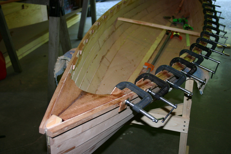 The decks are installed on each end and then cut to a rounded shape (for a comfortable hand hold), with tabs on each side to accept the inwale. The left side of the canoe in this photo shows the outwale and the small spacer blocks that are attached before the inwale is glued on. The clamps are holding the inwale which has just been attached on the right side of the canoe. Lots of clamps are needed!