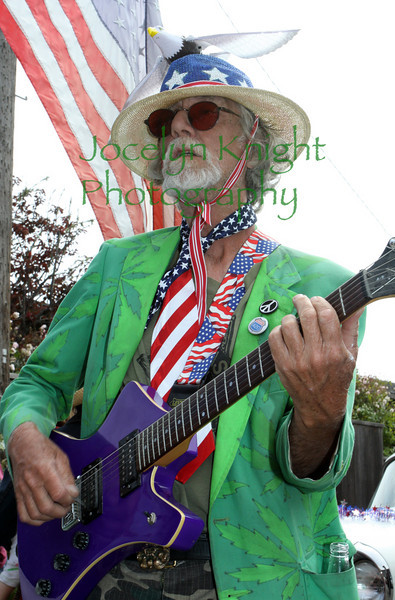 """StuArt plays electric guitar with friends in the Bolinas 4th of July Parade as they pass in front of Smiley's in downtown Bolinas, CA on July 4, 2010. StuArt described the Bolinas Parade as """"Like the Star Spangled Banner except played by Jimi Hendrix.""""(Special to the IJ/Jocelyn Knight)"""