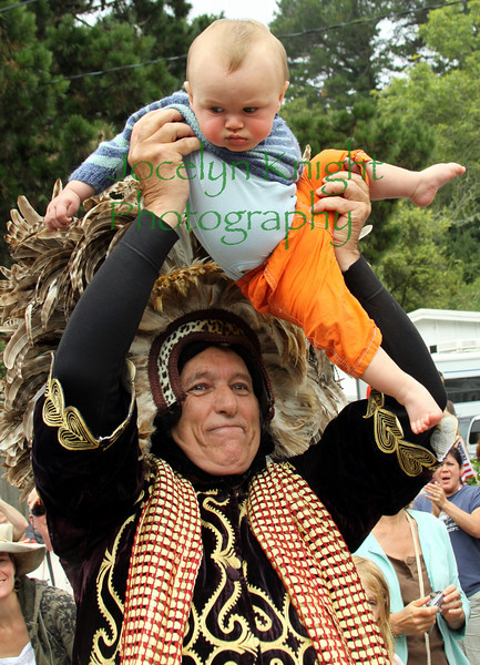 """Tom D'onofrio representing the Bolinas Sun Festival holds baby Fin McDonald high above the parade in downtown Bolinas, CA on July 4th, 2010. D'Onofrio said the group is not religious but is just expressing gratitude for life and """"we are not blessing the babies, the babies are blessing US...""""(Special to the IJ/Jocelyn Knight)"""