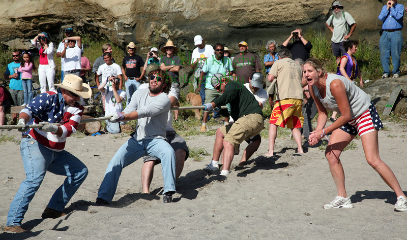 Joy Conway (right) cheers on the Bolinas Men's Team at the Bolinas Pull which  ended in momentary confusion as the official stopped the action just 4 minutes after it started when 4 to 5 men on the Stinson Beach team were on their knees and being dragged toward the water's edge. The official said the rules require everyone to be on their feet at all times, making Bolinas the  winner of the pull  July 4, 2010 in Bolinas, CA.(Special to the IJ/Jocelyn Knight)