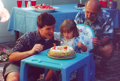 Paul and Grandpa Hal help Kayla to blow out the candles at her THIRD of three third birthday parties.  Yes - really. Palo Alto CA July 2000