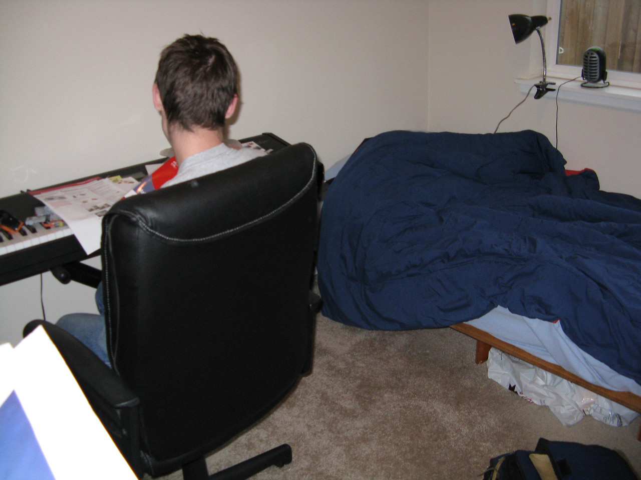 Kevin at his keyboard with his bed in the background.