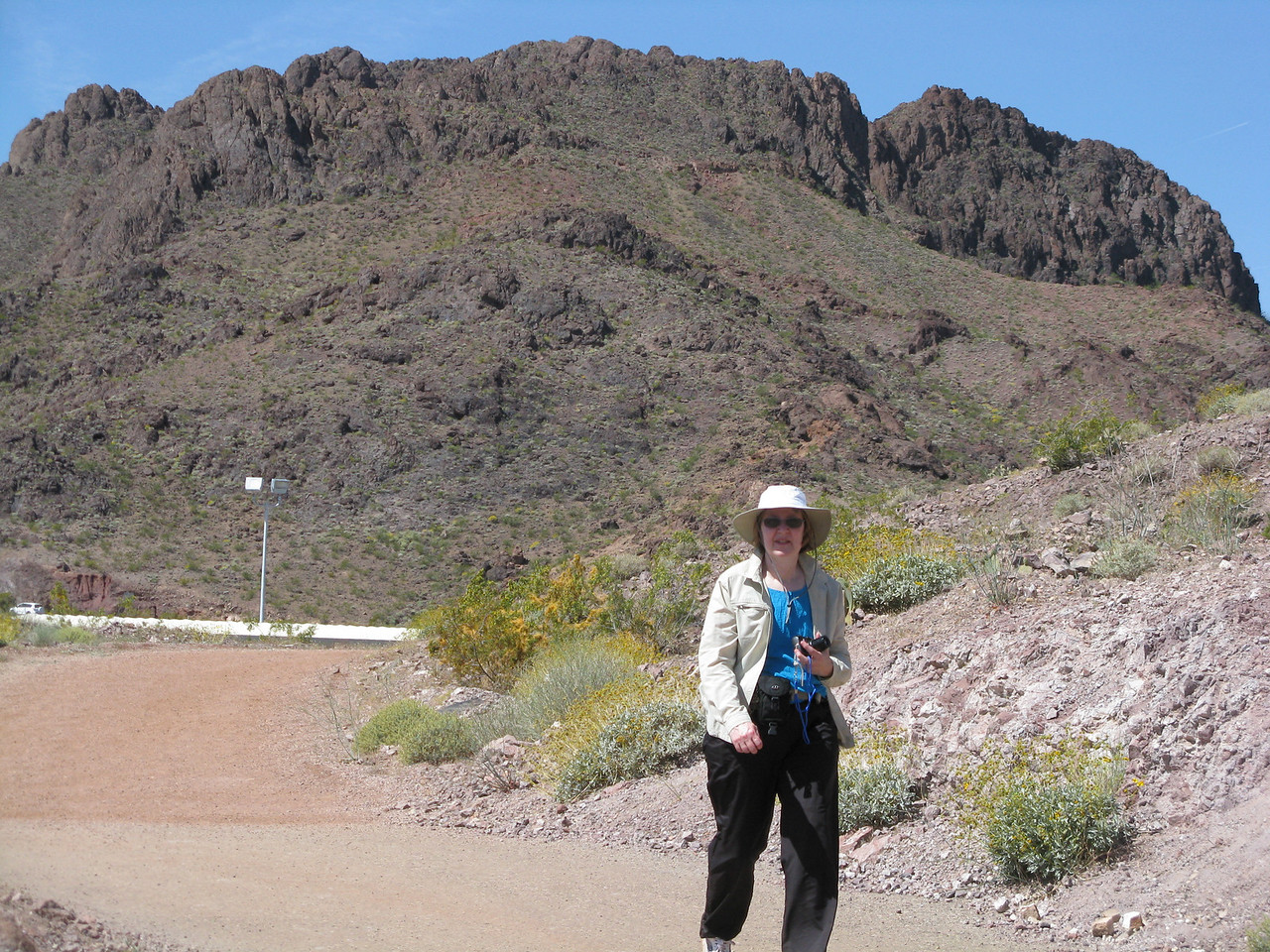 Mary is walking around a broad curve in the trail as she heads downhill towards Hoover Dam.