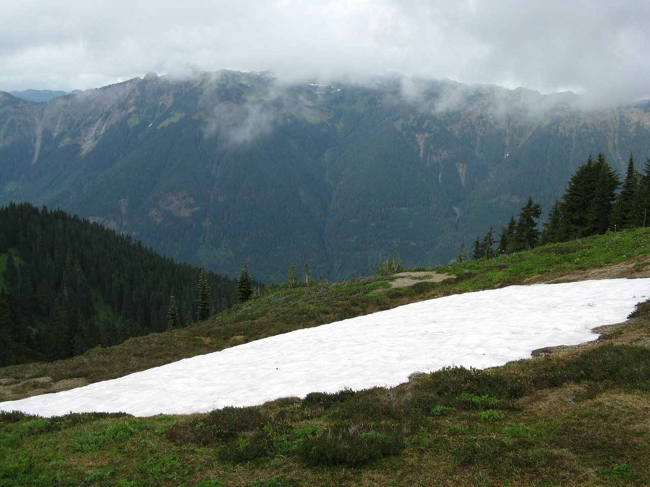 Looking across a small snow field to another ridge in the distance.