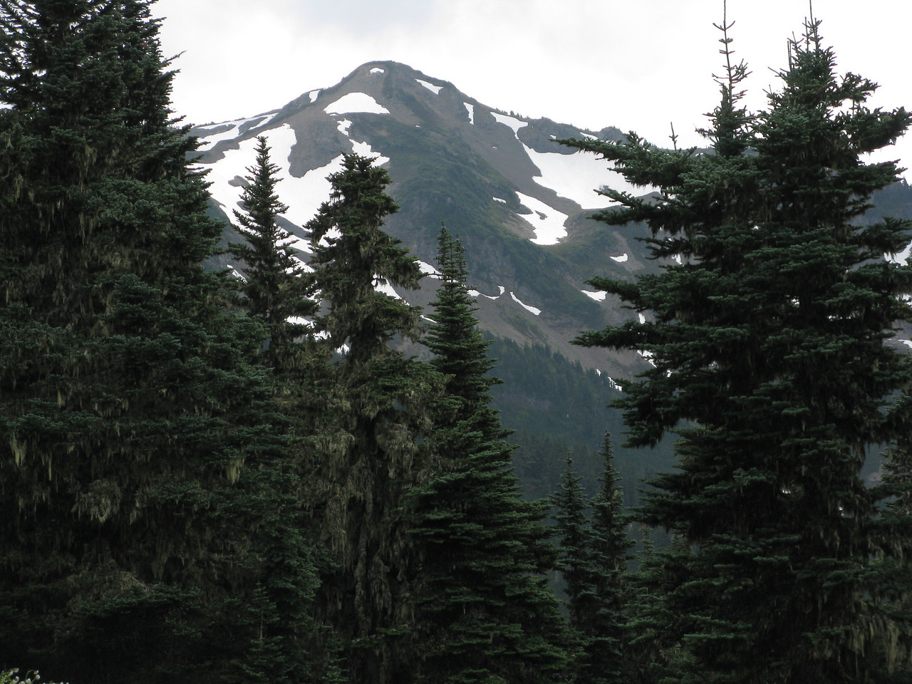 As we approach the ridge, we can see snow spotted mountains in the distance.