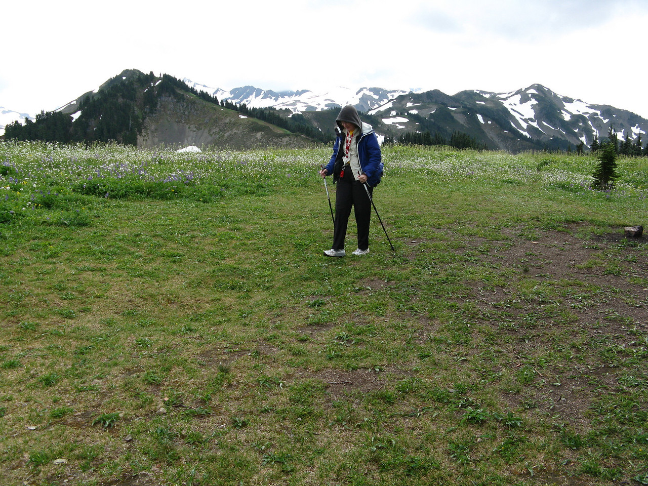 Mary is standing in front of Mount Baker, which is under the shroud of clouds.