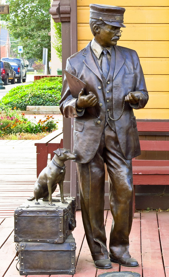 "This charming life-size bronze is titled the ""Stationmaster and Companion.""   It is found at the northeast corner on the trackside boardwalk of the  depot.  Keith McMasters, who is from eastern Washington, created the sculpture and installed it in 2010."