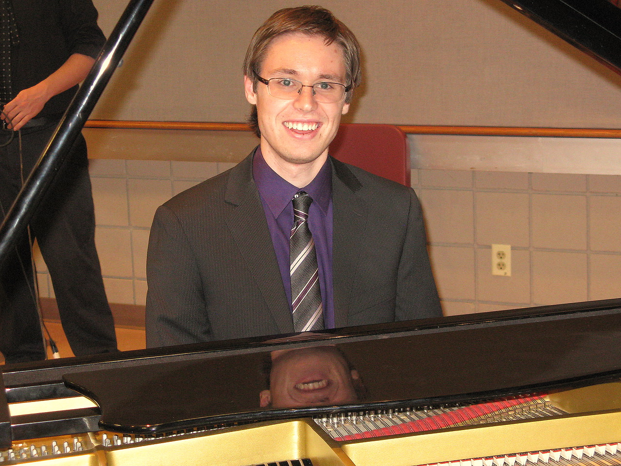 Kevin at the keboard of the baby grand piano.