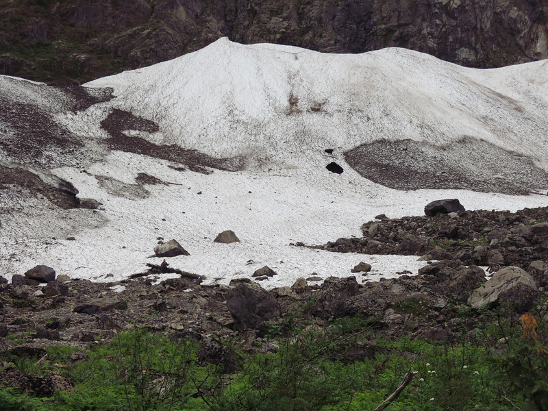 The snow field is huge relative to the person at the left center of the image.