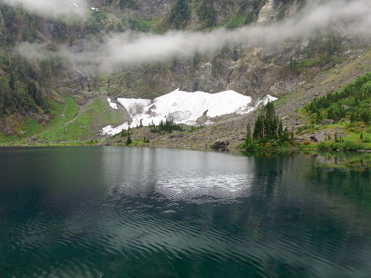 The lake, snow field, and low-hanging clouds.