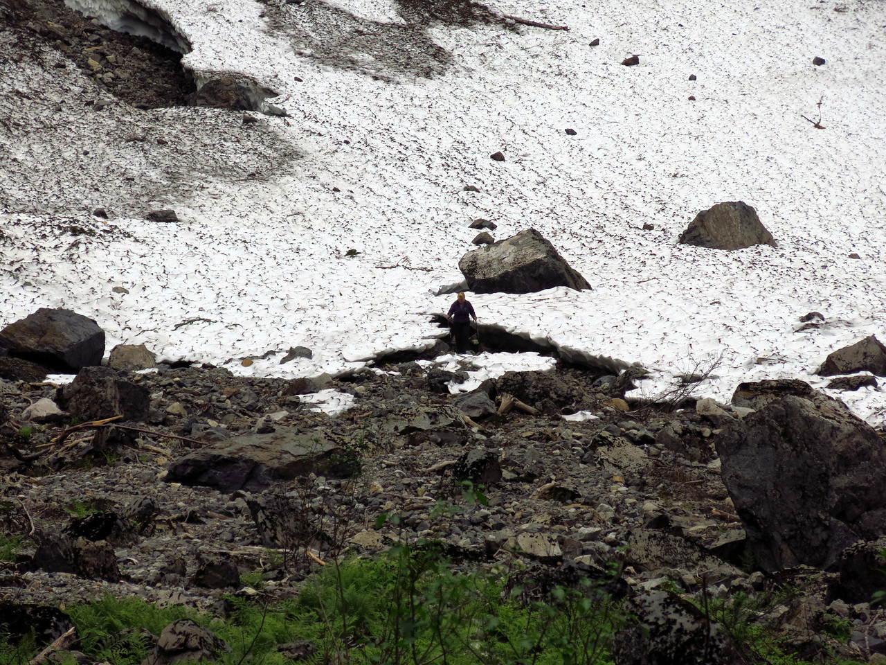 A telephoto view of the person (in the center of the picture).   She is standing at the edge of the snowfield.