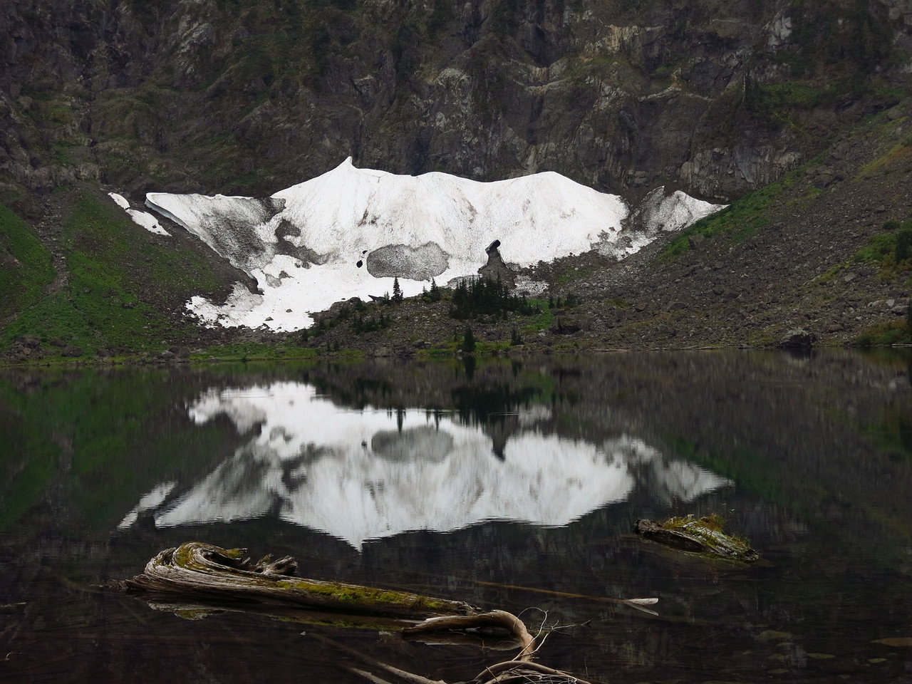 A dirty snow field lies at the opposite end of the lake with its reflection on the water.   The snow has collected from countless avalanches at the base of the north face of Mount Pilchuck.  The snow is not a glacier.  In hot and dry years, the snow field may completely melt away by the end of August.