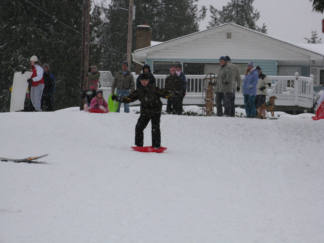 This young man is trying to use a disk as a snowboard.  He does not have much control.  It is hard to get an edge in the compact snow, because there are no edges on the disk.