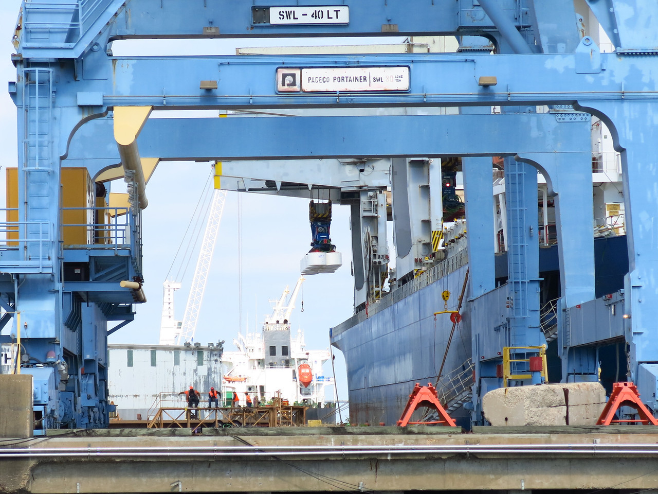White material is being loaded by a crane attached to the ship