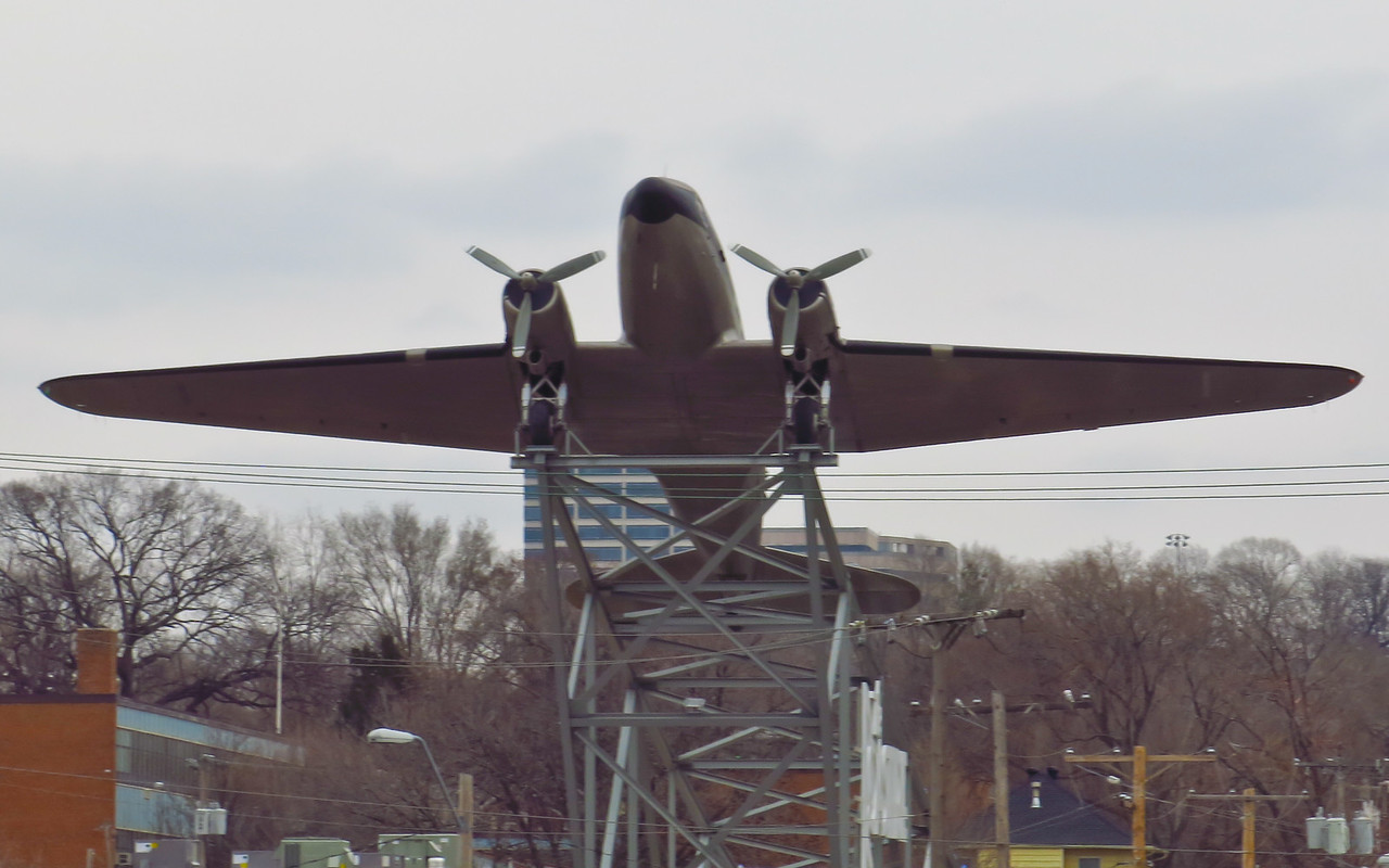 """Wihin view from the rondhouse is this full scale model of a DC-3 passenger plane from the 1950s.  It sat on top of a building that houses a company the sells a proprietary brand of  """"air-roasted"""" coffee."""
