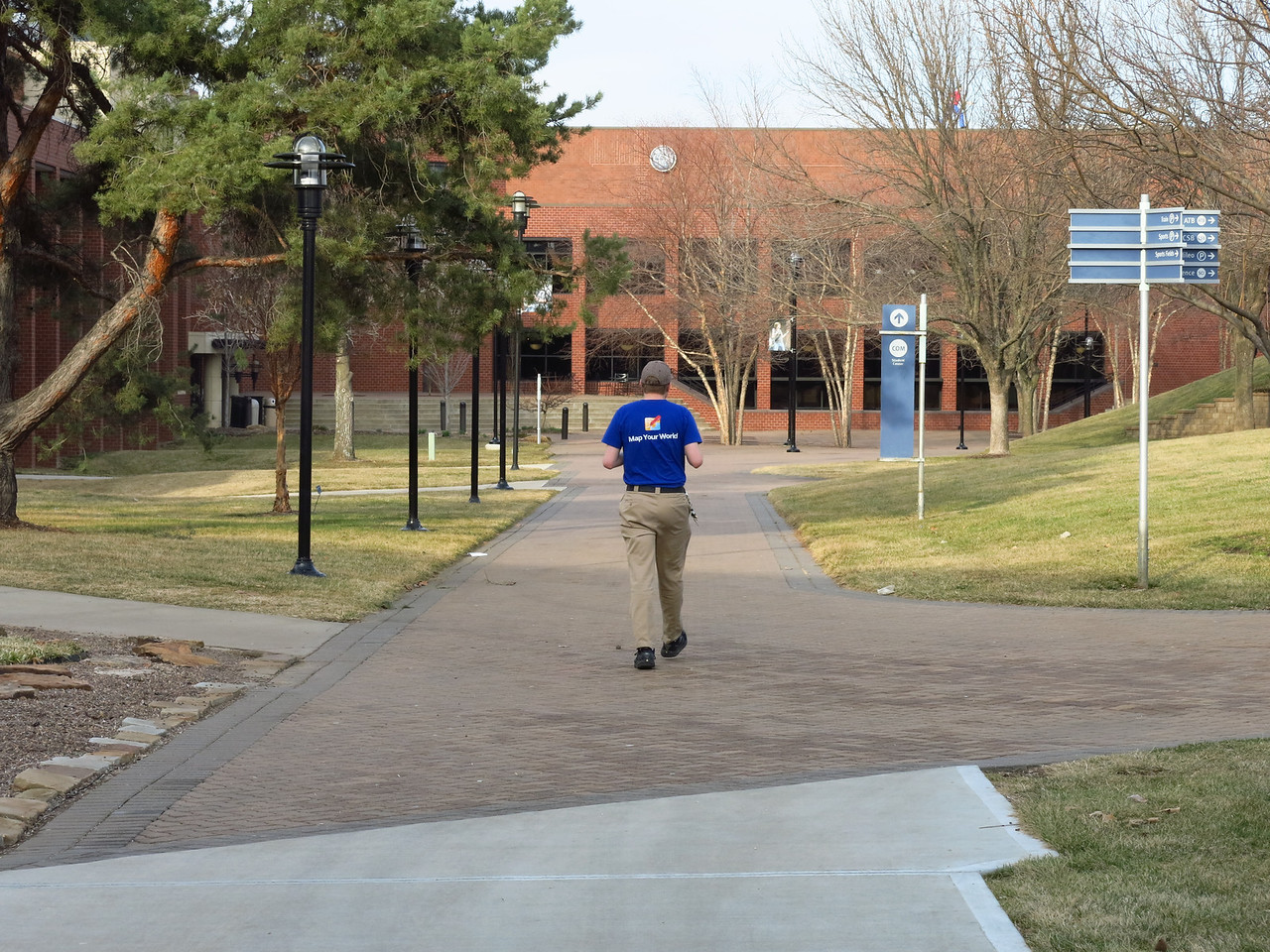 Nathan is striding down the main walkway of the central campus at JCCC.  On Friday, March 15, the high was 78 degrees.  On Sunday, March 17, it was snowing lightly.