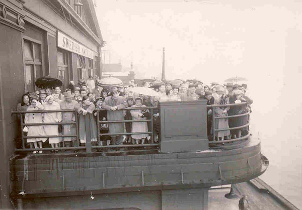 September, 1957 Henry Kuck arriving on ship from Germany (far left, wearing hat, under umbrella).