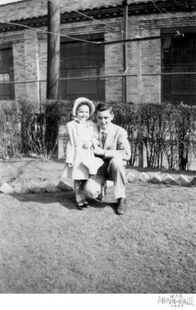 March 25, 1951 1226 Ohio Avenue, Trenton, NJ Loretta Kusek and cousin, John Joseph Szymanski, Jr. Taken in the back yard of the Kusek house located on Ohio Avenue. The factory in the backgound is Heinamen's Electric Company.