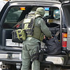 SWAT team member suiting up from the back of a personal vehicle.