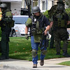 Well equipped SWAT members have Israeli automatic weapons, radios, and two layers of flack jackets.