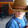 Little boy in overalls wearing a cowboy hat.