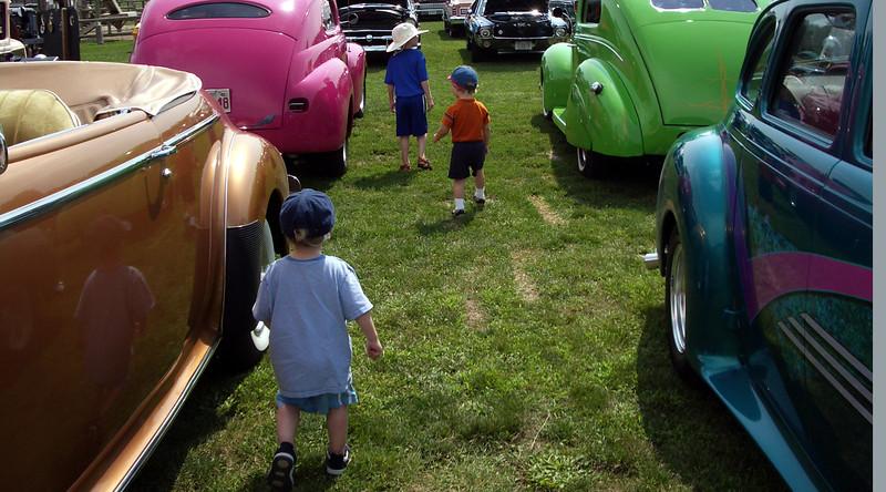 Children investigate at a vintage car show.