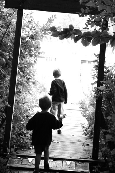 Two boys walk into the light in this dramatic black and white, high key image.