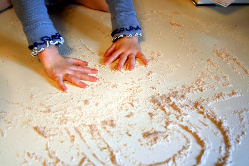 Little girl plays in flour.